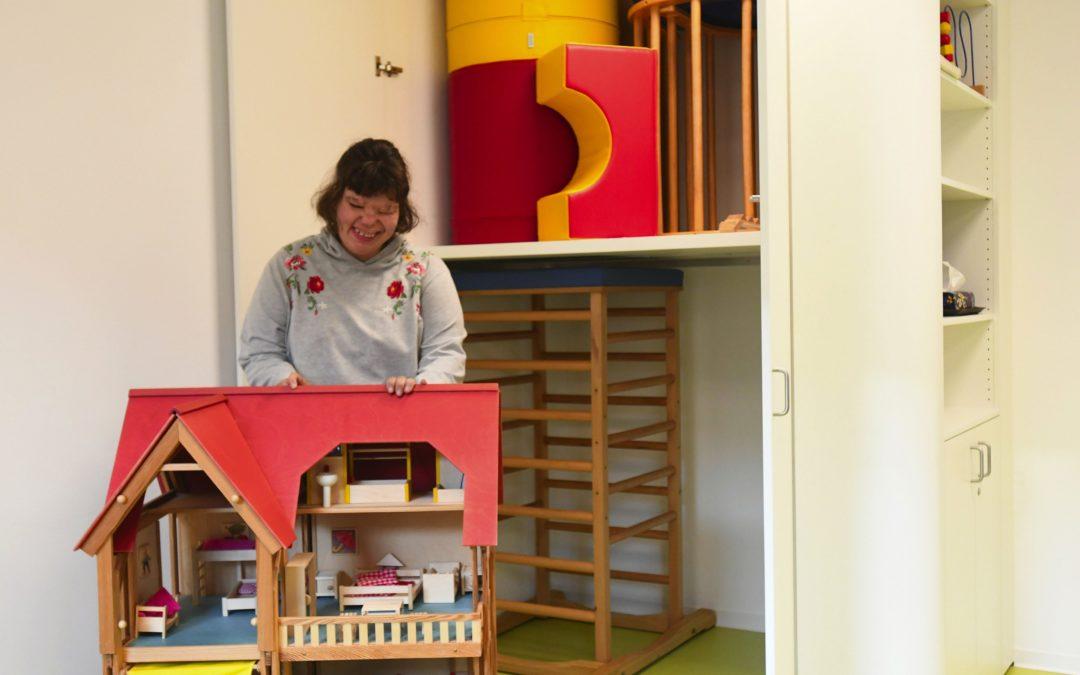Marie holt das große Puppenhaus aus dem maßgefertigten Spieleschrank, der jetzt in den Räumen der Frühförderung der Lebenshilfe in Marxheim eingebaut wurde. Die weiche Rundung des Möbelstücks senkt die Verletzungsgefahr, wenn die kleinen Kinder mal umhertoben. Foto: Knapp